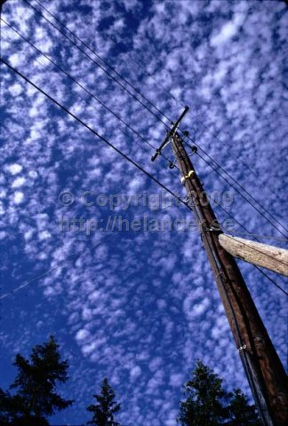 Telephone pole with clouds in the sky. (1971)